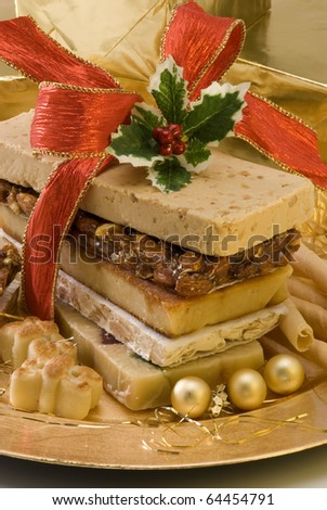 Typical Spanish Christmas nougat in a golden plate. - stock photo