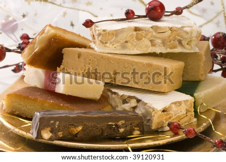 Typical spanish Christmas nougat in a golden plate. Selective focus. - stock photo