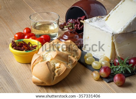 Typical Spanish Manchego cheese with grapes, mint and rosemary,bread and chili