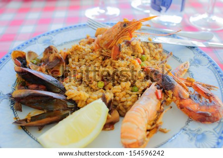 Typical spanish seafood paella, served in a restaurant in Costa Brava - stock photo