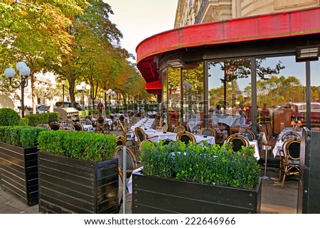 Typical street Parisian cafe with a reflection in the windows of the symbol of Paris - the Eiffel Tower, Paris, France - stock photo