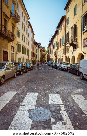 Typical street, urban street, street way with street buildings and street cars, street in Italy, Europe - stock photo