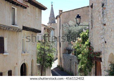 Typical street with old houses and bell tower of a village in La Provence, wooden doors, windows, old street lamps, beautiful view, outdoors - stock photo