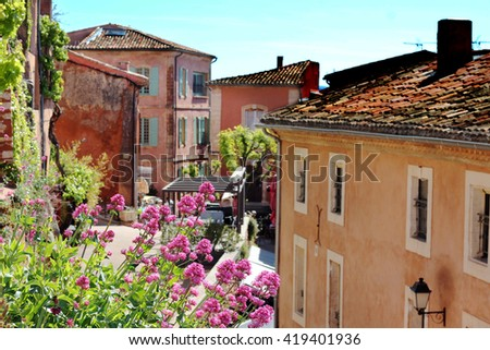 Typical street with old houses of a village in La Provence, wooden window, beautiful view, focus on the flowers, blurred background, outdoors - stock photo