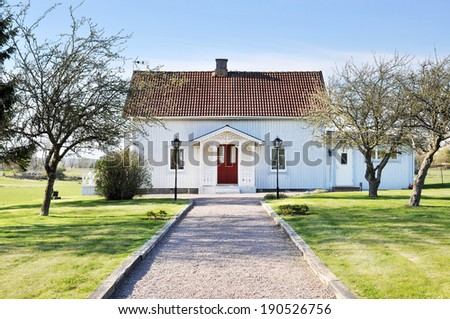 Typical swedish white summerhouse with a garden. - stock photo
