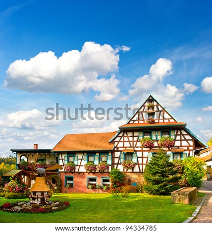 typical traditional house in the Black Forest, Southern Germany. european landscape with flowers garden and cloudy blue sky - stock photo