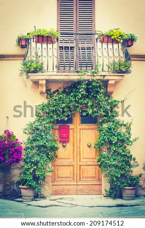 Typical Tuscan door with plants and  balcony in vintage filter - stock photo