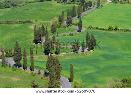 Typical Tuscany landscape with curvy road, rolled hills and many cypress. - stock photo
