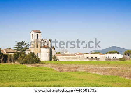 Typical tuscany romanesque church surrounded by a field near a cemetery (Italy - Pisa) - stock photo