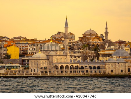 Typical urban landscape with old mosques in arabic town. Seaside view of Istanbul at sunset, islamic architecture in urban structure. Cultural tradition of islam religion in turkish city. - stock photo