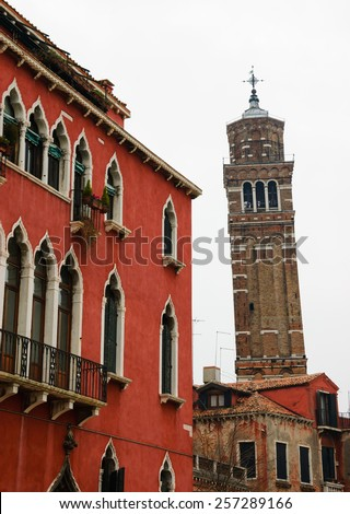 Typical Venetian building and leaning bell tower at backgrounds. Cloudy winter day. Venice, Italy. - stock photo