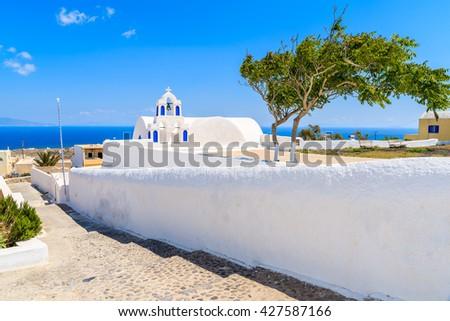 Typical white church on street of Oia town on Santorini island, Cyclades, Greece - stock photo