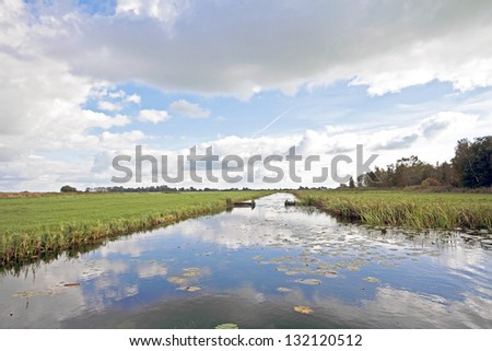 Typical wide dutch landscape with meadows, water and cloudscapes - stock photo