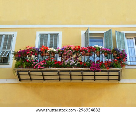 Typical windows with open wooden shutters and balcony, decorated with fresh colorful Flowers of medieval House in Nice, Provence, France. - stock photo