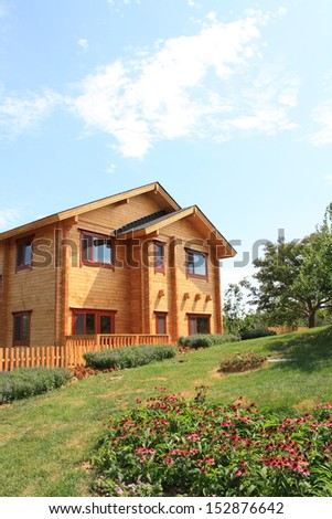 Typical wooden country house with lawn - stock photo