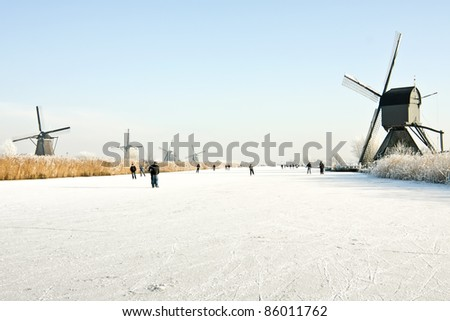 Typically dutch: ice skating on a frozen lake at Kinderdijk with view on a windmill on a cold winterday - stock photo