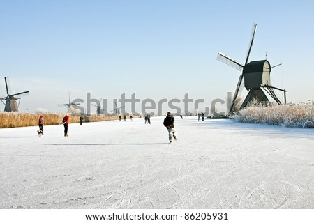 Typically dutch: ice skating on a frozen lake at Kinderdijk with view on a windmill on a cold winterday in the Netherlands - stock photo