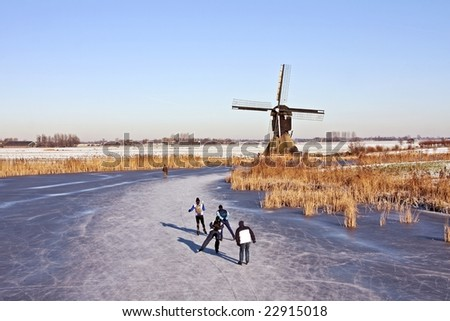 Typically dutch: ice skating on a frozen lake with view on a windmill on a cold winterday in the Netherlands - stock photo