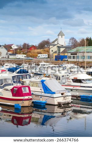 Typically Norwegian fishing village landscape. Small boats are moored in marina - stock photo