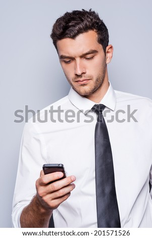 Typing business message. Confident young man in shirt and tie holding mobile phone and looking at it while standing against grey background  - stock photo