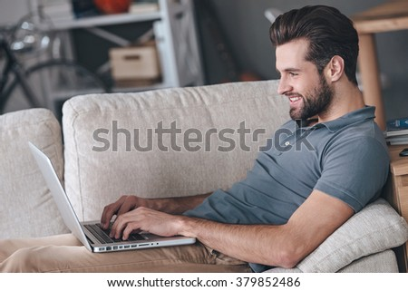 Typing new blog post. Side view of handsome young man using his laptop with smile while sitting on the couch at home - stock photo