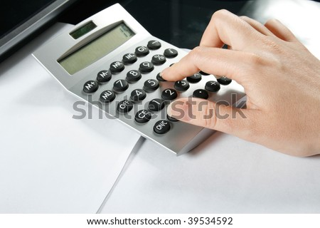 Typing numbers for income tax return with calculator - stock photo
