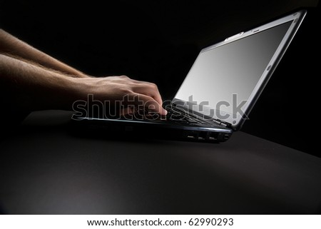 typing on the keyboard of a laptop against a black background - stock photo