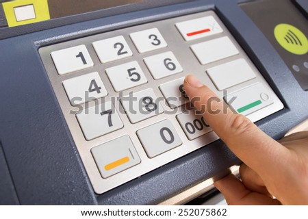 typing security PIN code on an ATM to withdraw money - stock photo