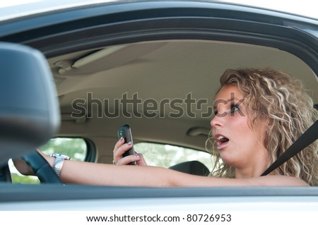 Typing SMS while driving car - stock photo