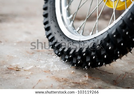 Tyre of motocross bike on ice and snow on background, selective focus on the middle part - stock photo