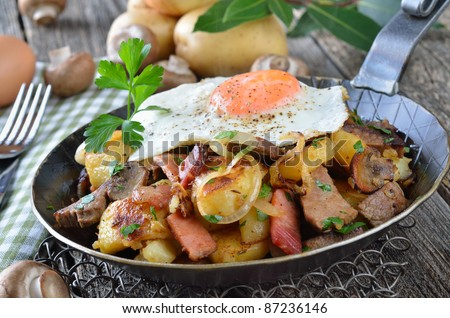 "Tyrolean fried potatoes with meat, bacon, mushrooms and a fried egg (Tyrolean ""Groestl"") - stock photo"