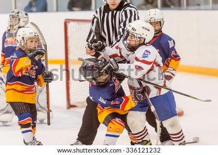 Tyumen, Russia - April 14, 2013: Hockey tournament among children teams till 9 years old. Game between Rubin 04 (Tyumen) and Metallurg 04 (Magnitogorsk). Referee separates fighting players - stock photo