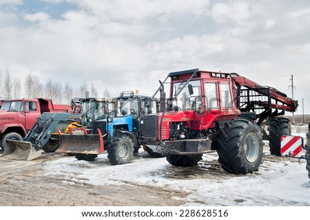 "Tyumen, Russia - April 04. 2014: IV Tyumen specialized exhibition ""Agricultural Machinery and Equipment"". Tractors and truck stand on open area - stock photo"