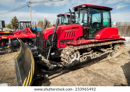 "Tyumen, Russia - April 04. 2014: IV Tyumen specialized exhibition ""Agricultural Machinery and Equipment"". Plow tractor demonstration of Belarus production on platform open-air - stock photo"