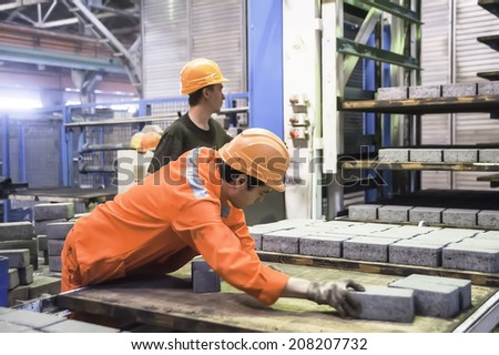 Tyumen, Russia - August 13, 2013: Block making department at construction material factory ZHBI-5. Workers at the machine on stone blocks drying - stock photo