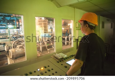 Tyumen, Russia - August 13, 2013: Block making department at construction material factory ZHBI-5. Engineer operate production conveyor from management room