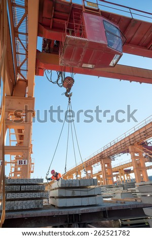 Tyumen, Russia - August 13, 2013: Finished goods warehouse at Concrete Goods Plant No. 5. Slinger accepts plates from crane operator to loading railway car - stock photo