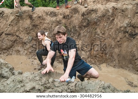 Tyumen, Russia - August 8, 2015: Steel Character command extrim race project is running on extreme obstacle course. Stage mud hole - stock photo