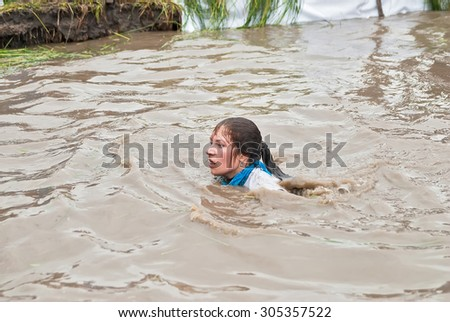 Tyumen, Russia - August 8, 2015: Steel Character extrim race on Krugloe lake. Gagarin park in Cape district. Obstacle stage - to get on wall and to jump in water. Woman swims after jump - stock photo