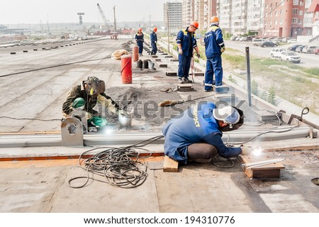 Tyumen, Russia - July 31, 2013: JSC Mostostroy-11. Bridge construction for outcome of Melnikayte street and Shirotnaya streei in Tyumen. Welders work at bridge span joints - stock photo