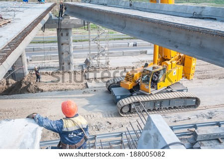 Tyumen, Russia - July 31, 2013: JSC Mostostroy-11. Bridge construction for outcome of the Tobolsk path and Bypass road round Tyumen. Workers levels provision of plate which keeps within on bridge span