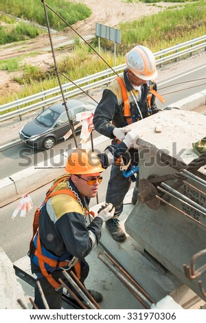 Tyumen, Russia - July 31, 2013: JSC Mostostroy-11. Bridge construction for outcome of the Tobolsk path and Bypass road round Tyumen. Builder workers in safety protective equipment - stock photo