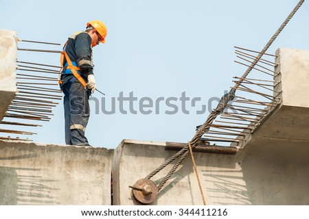 Tyumen, Russia - July 31, 2013: JSC Mostostroy-11. Bridge construction for outcome of the Tobolsk path and Bypass road round Tyumen. Builder Worker in safety protective equipment on bridge - stock photo