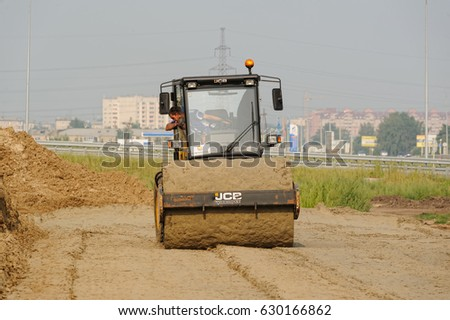 Tyumen, Russia - July 31, 2013: JSC Mostostroy-11. Bridge construction for outcome of the Tobolsk path and Bypass road round Tyumen. Road roller compressing sand to highway construction