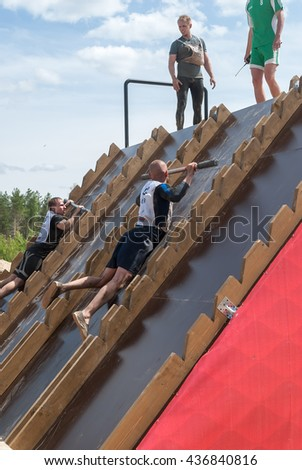 Tyumen, Russia - June 11, 2016: Race of Heroes project on the ground of the highest military and engineering school. Athlete gets on inclined wall by means of bar - stock photo