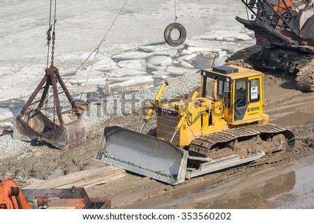 Tyumen, Russia - March 29, 2008: Construction of pedestrian quay on Tura river. Digger, heavy duty construction equipment parked at work site - stock photo