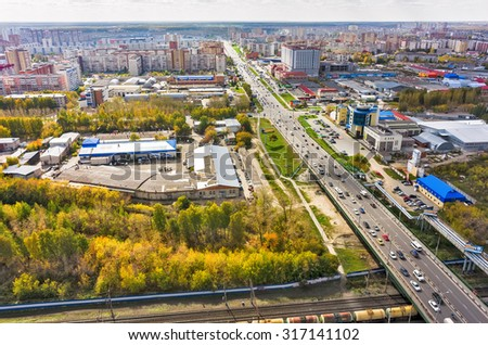 Tyumen, Russia - May 14, 2015: Aerial view on city quarters. Melnikayte and 30 let Pobedy streets intersection, industral area, bridge over railways. Autumn season