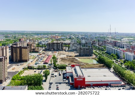 Tyumen, Russia - May 25, 2015: Aerial view onto Magnet hypermarket and Central and Novin residential district construction. Between 50 let Oktyabrya and Harkovskaya streets - stock photo