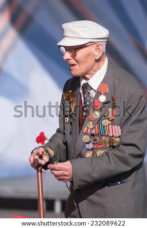 Tyumen, Russia - May 9. 2009: Victory Day in Tyumen. Old veteran of World War II at tribunes waiting for parade - stock photo