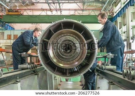 Tyumen, Russia - November 14, 2007: JSC Tyumenskie Motorostroiteli (Plant on production and repair of aviation engines). Workers assembly aviation engine - stock photo